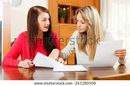 serious women looking financial documents in home or office