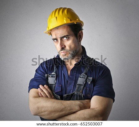 Serious worker with yellow helmet and work suit