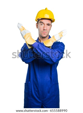 Serious workman doing a gesture of prohibition on white background