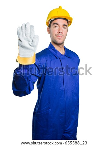 Serious workman with a stop gesture on white background