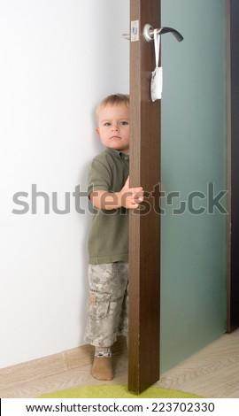 Serious 2-year boy handling a door - stock photo