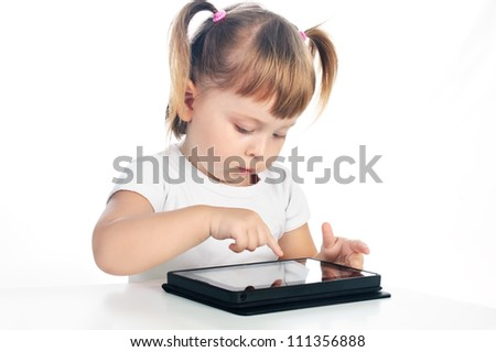 serious 3 years old girl touching screen on tablet isolated over white - stock photo
