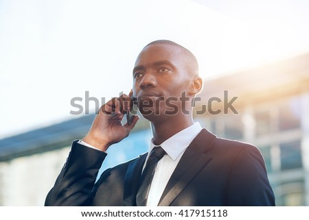 Serious young African man in suit using phone with sunflare - stock photo