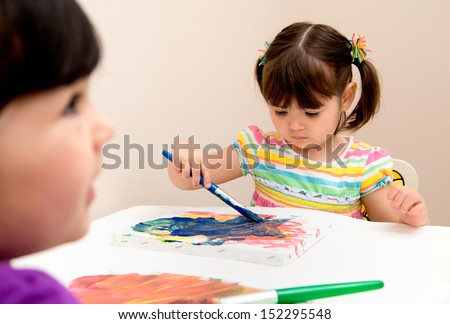 Serious young artist focused on her painting as her sister watches - stock photo