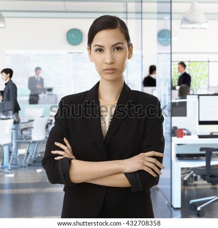 Serious young asian businesswoman at busy corporate office. - stock photo