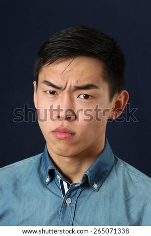 Serious young Asian man looking at camera - stock photo
