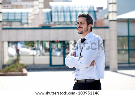 Serious young attractive businessman thinking, outdoor