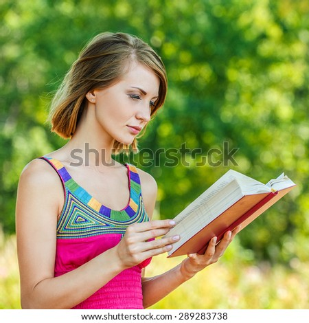 serious young beautiful short-haired woman holding red book looking sideways background summer green park - stock photo