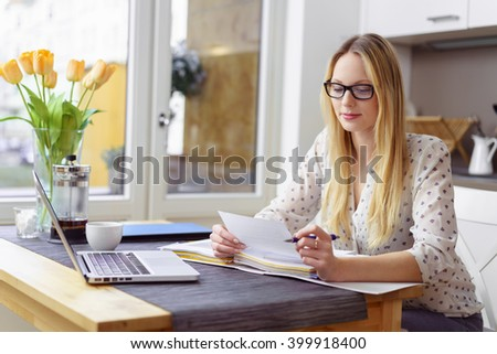 Serious young blond woman wearing eyeglasses sitting at little table with laptop and financial statements in kitchen next to bright window - stock photo