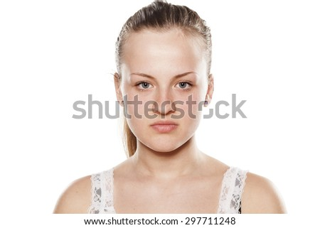 Serious young blonde without make up looking at the camera - stock photo