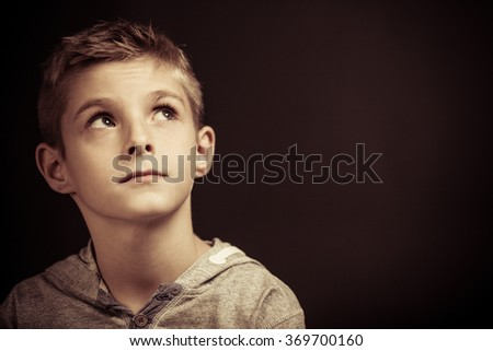 Serious young boy sitting thinking looking up into the air with a pensive expression, head and shoulders over a dark background with copy space - stock photo
