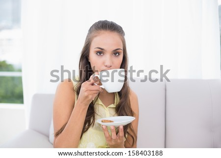 Serious young brunette drinking from a cup in bright living room