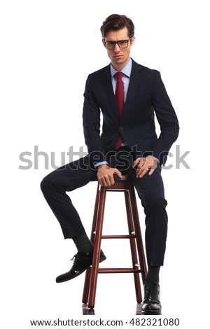 serious young business man wearing glasses is sitting on a chair and looks ath the camera, full body picture isolated on white background