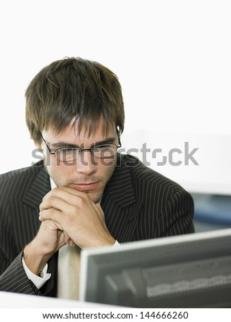 Serious young businessman looking at computer in office - stock photo
