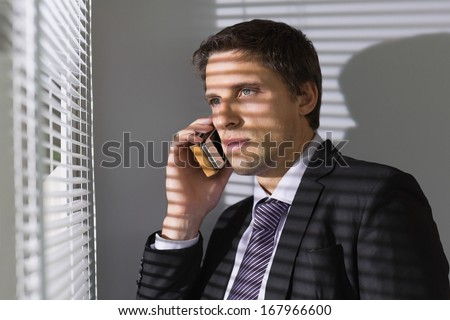 Serious young businessman peeking through blinds while on call in the office - stock photo