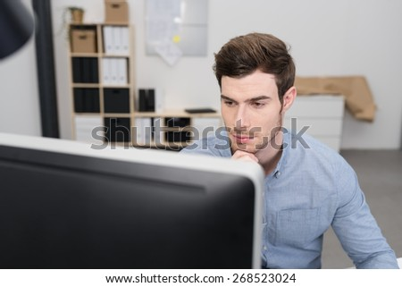 Serious young businessman reading his computer screen with a glum expression and his chin resting on his hand, view over the top of the monitor - stock photo