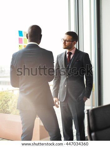 Serious young businessman wearing glasses standing in front of a bright window overlooking a patio talking to an African colleague - stock photo