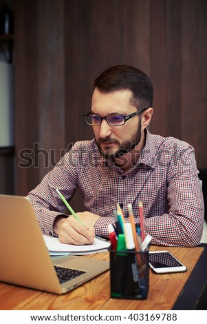 Serious young businessman with the glasses sitting and using laptop at office and taking notes - stock photo