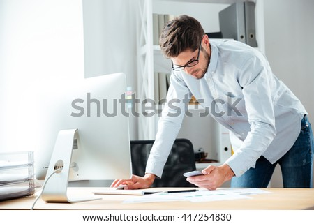 Serious young businessman working with computer and using cell phone in office
