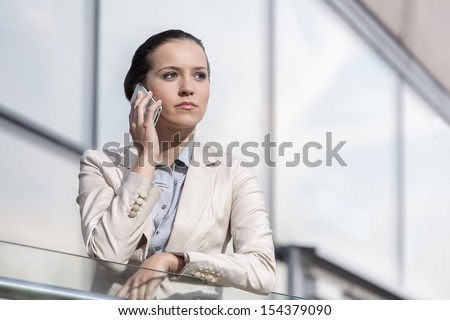 Serious young businesswoman using cell phone at office railing - stock photo