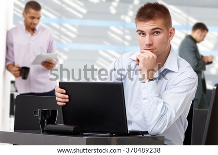 Serious young casual business team leader with laptop at office, sitting at table, colleagues in background, looking at camera, hand under chin. - stock photo