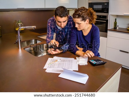 Serious young couple reviewing their bank accounts with a digital tablet and calculator at home. Financial family concept. - stock photo