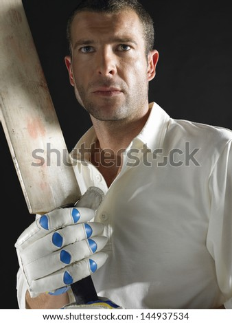 Serious young cricket player with bat against black background - stock photo