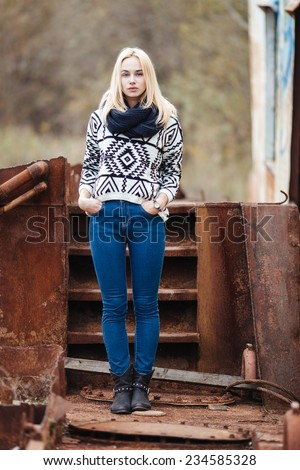 Serious young cute lady in sweater and scarf outdoors full length portrait in abandoned place - stock photo