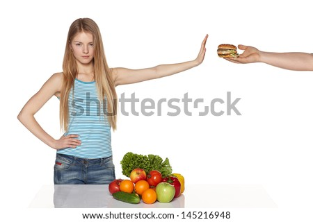 Serious young female refusing fast food, against white background