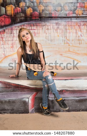 Serious young female skateboarder in sleeveless top