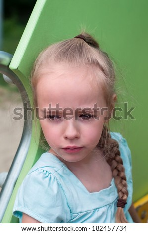 Serious young girl sitting on the playground - stock photo
