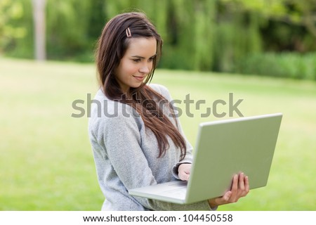Serious young girl standing in a public garden while working on her laptop