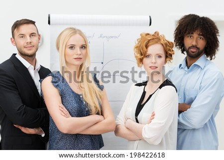 Serious young group of business men and women standing facing the camera with folded arms in front of a flip chart