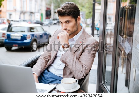 Serious young handsome businessman holding cup of coffee and working with laptop in cafe outdoors - stock photo