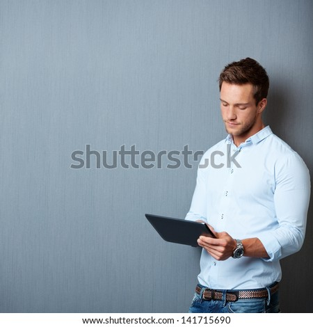 Serious young male executive using digital tablet against gray background - stock photo