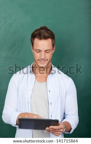 Serious young male executive using digital tablet against green background