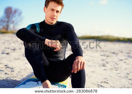 Serious young male surfer sitting on his surfboard on a sandy beach in his wetsuit looking at the camera with a thoughtful expression, with copyspace