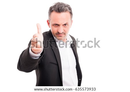 Serious young man doing a shoot gun gesture in your direction isolated on white background