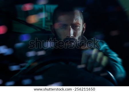 Serious young man driving a car at night. Bokeh lights reflecting from the windshield, motion blur