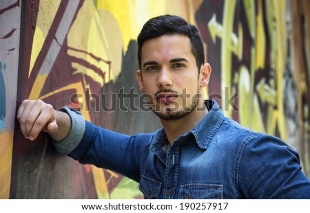 Serious young man leaning on colorful graffiti wall, looking at camera