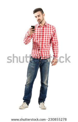 Serious young man looking on his smartphone. Full body length portrait isolated over white background.  - stock photo