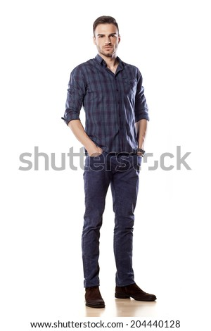serious young man posing with his hands in pockets - stock photo