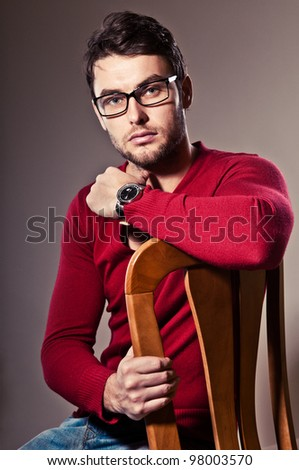 serious young man, sitting in his chair and stares - stock photo