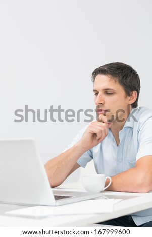Serious young man using laptop in living room at home