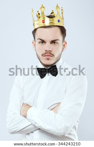Serious young man, with beard and mustaches, wearing in white shirt, bow and gold crown, posing with hands crossed on his chest, on white background, in studio, waist up - stock photo