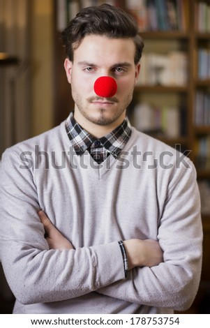 Serious young man with red clown nose, arms crossed, indoor shot - stock photo