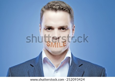 Serious young man without a mouth on a blue background with the words: Smile - stock photo