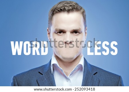 Serious young man without a mouth on a blue background with the words: Wordless - stock photo