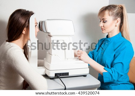 serious young ophthalmologist check the eye of the patient on this machine to check the vision. Ophthalmologist. medical, health, ophthalmology concept.