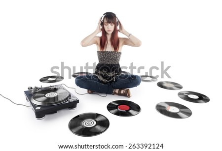 Serious Young Pretty Woman Sitting on the Floor Listening Music on a Vinyl Turntable with Vinyl Records Scattered on the Sides. Isolated on White Background. - stock photo